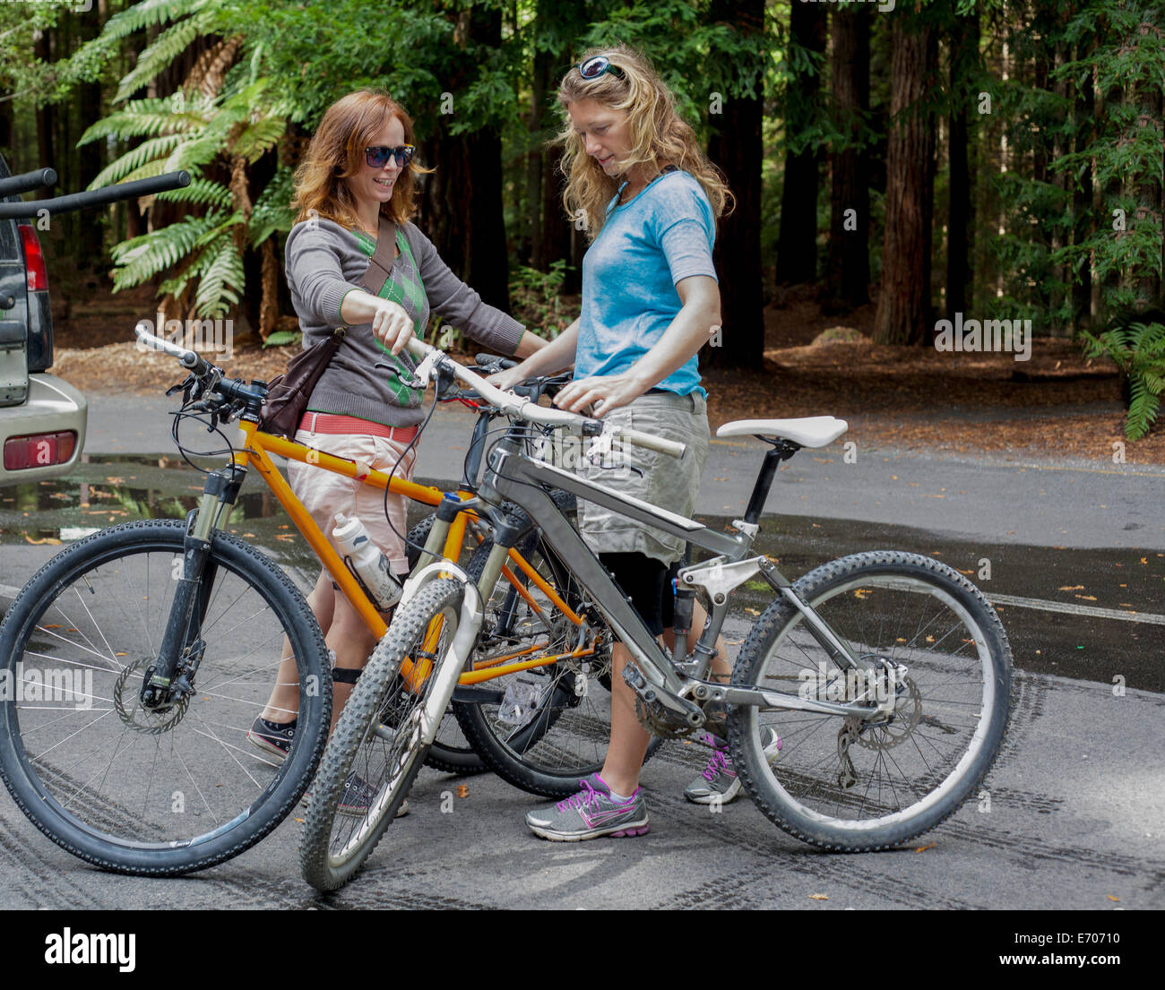 Two women mountain bikers preparing to cycle in forest - Stock Image