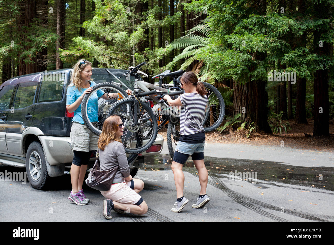 Three women mountain bikers lifting bikes from four wheel vehicle in forest - Stock Image