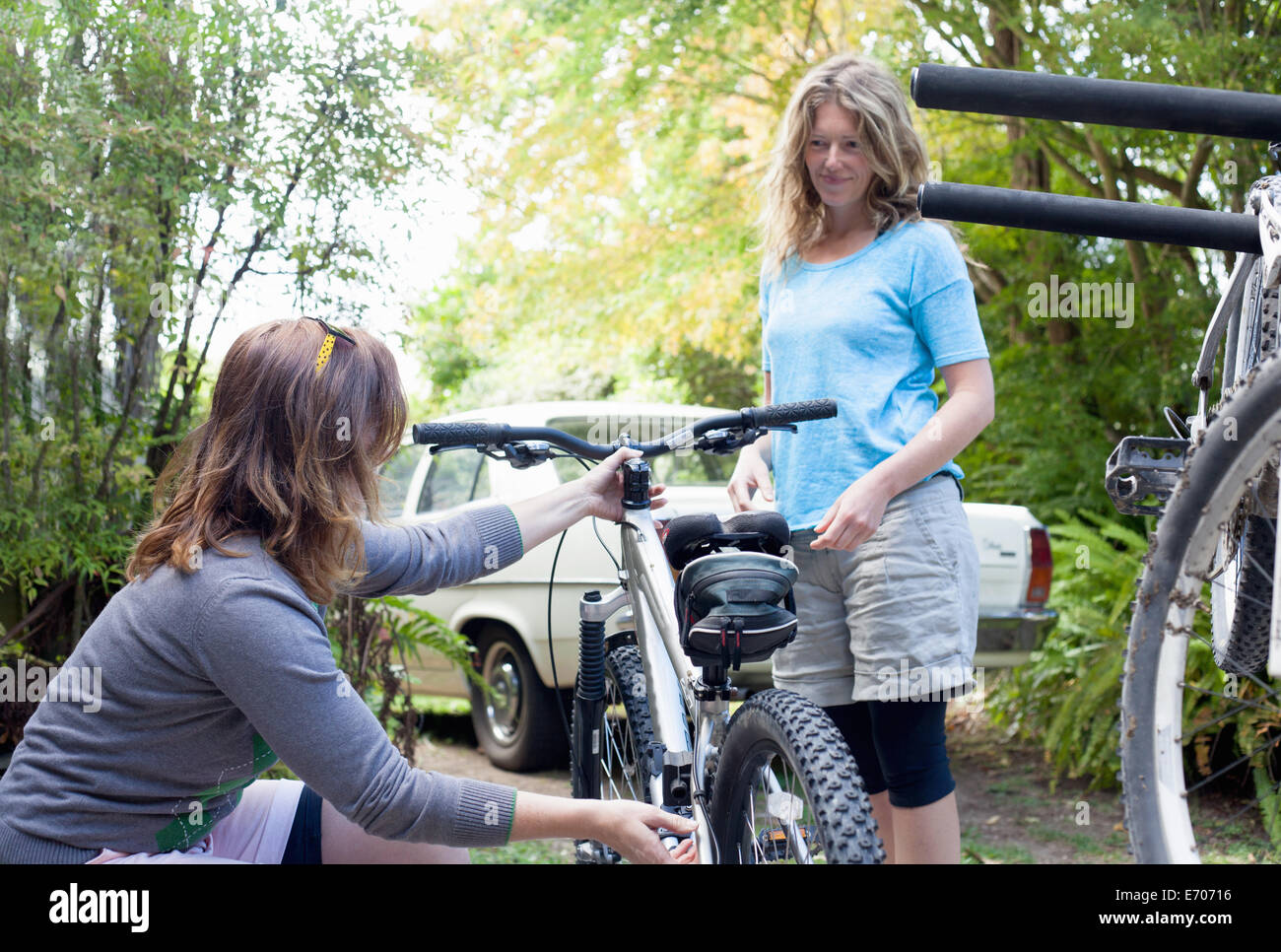 Two women mountain bikers checking cycles in forest - Stock Image