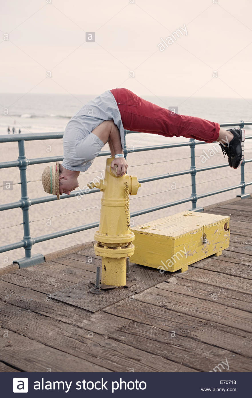 Young man doing push ups on fire hydrant, Santa Monica, California, USA - Stock Image