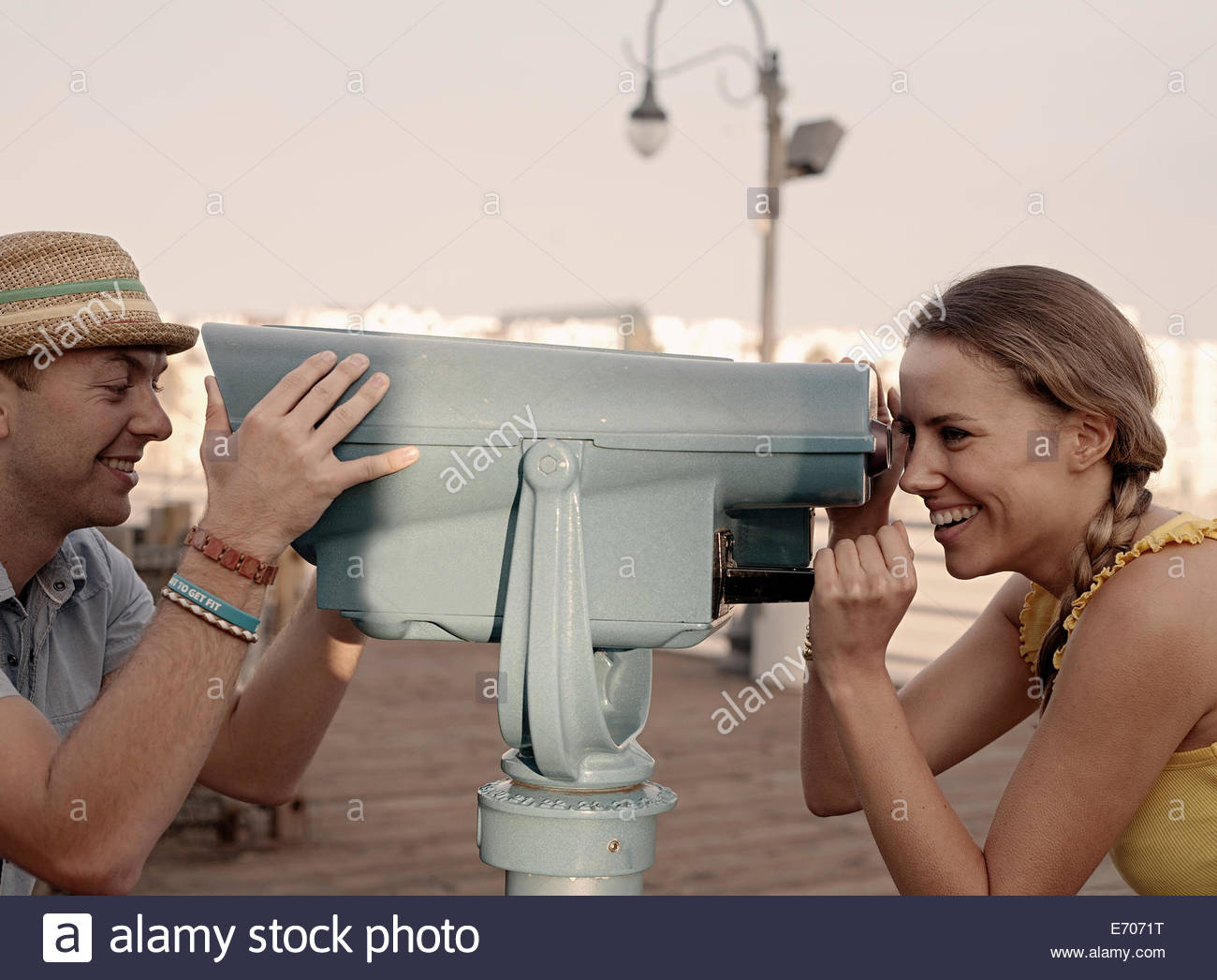 Young couple looking at each other through coin binoculars on Santa Monica pier, California, USA - Stock Image