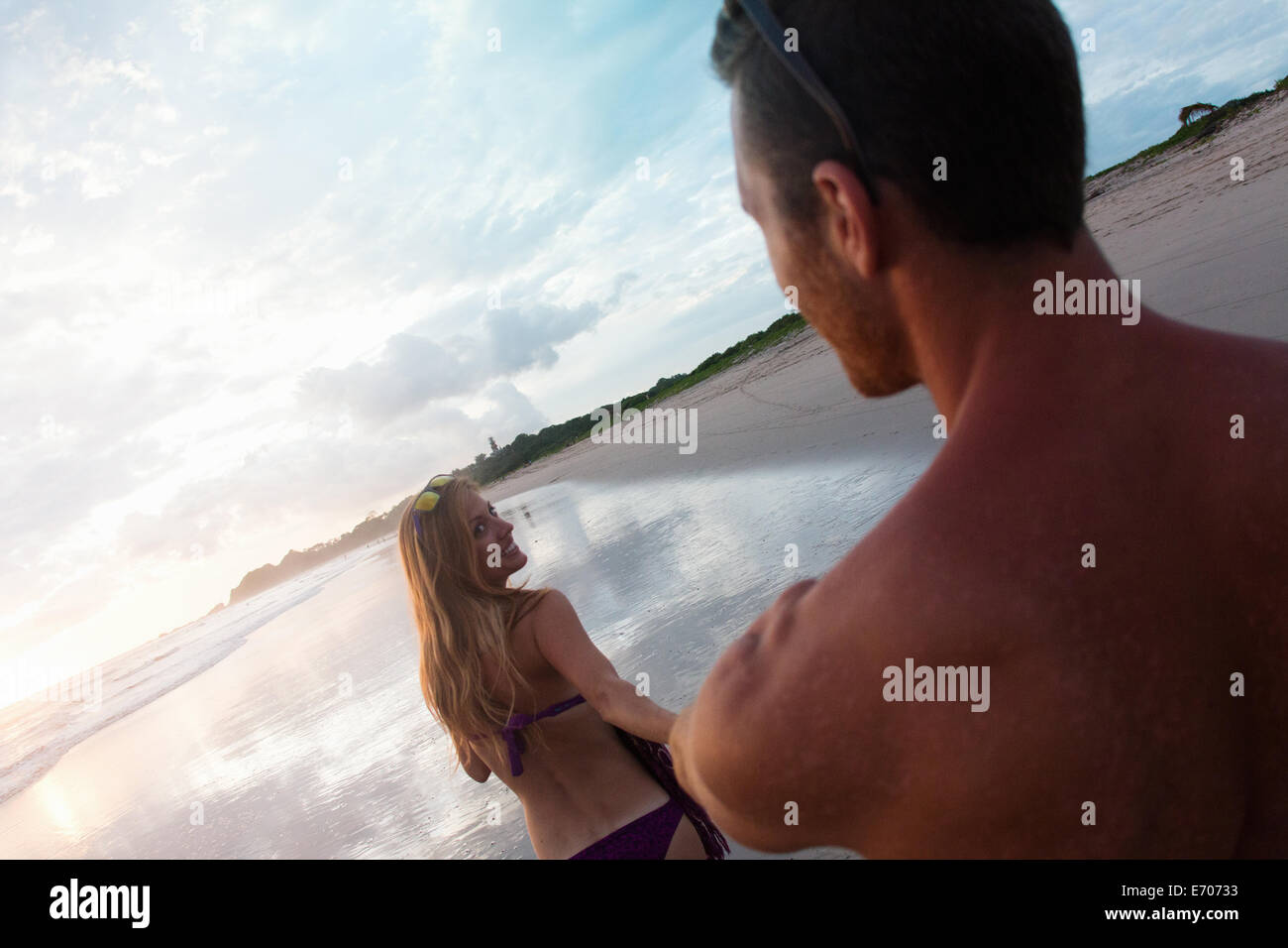 Over shoulder view of mid adult woman leading boyfriend by hand on beach, Nosara, Guanacaste, Costa Rica - Stock Image