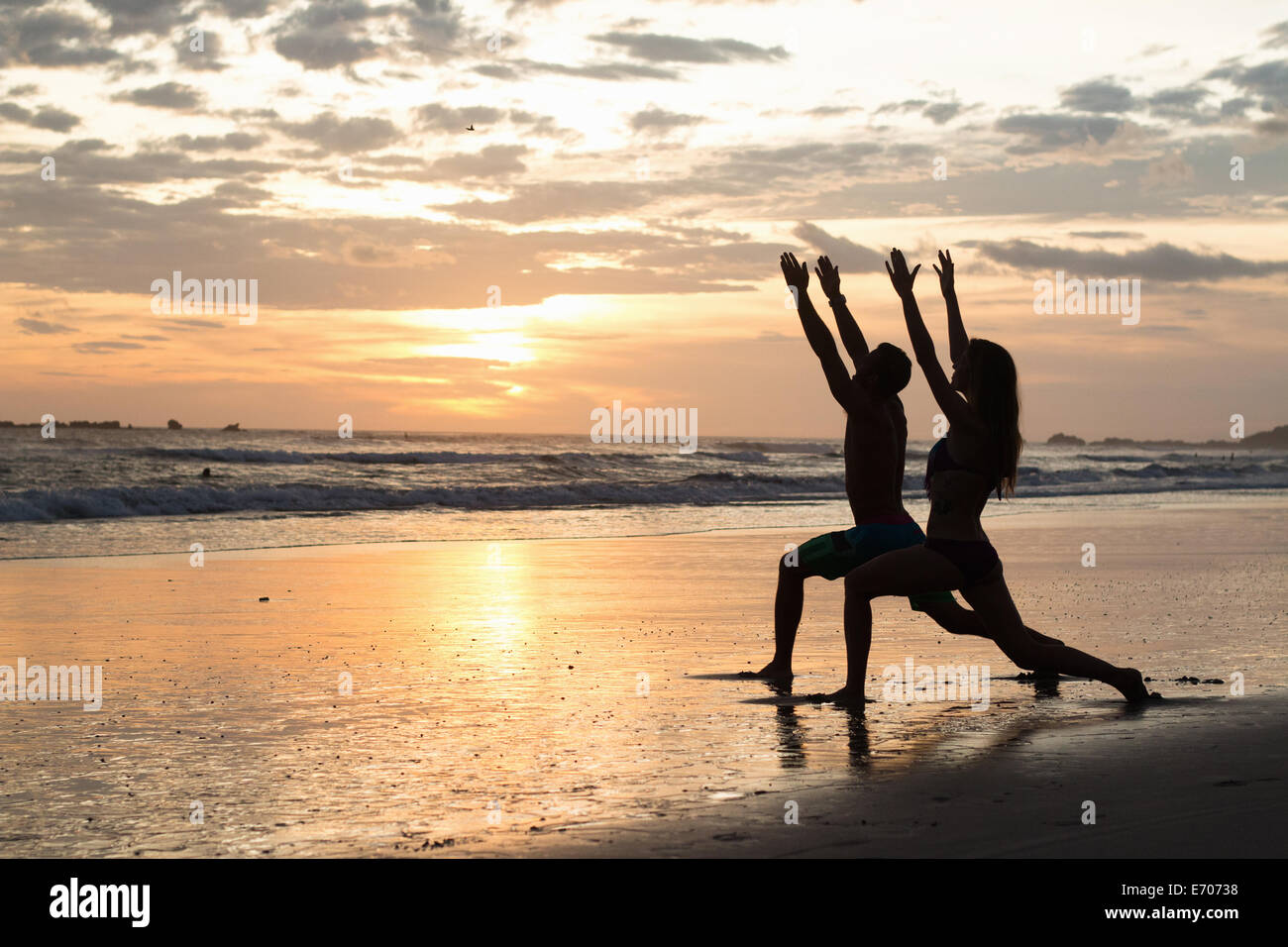 Couple doing stretching exercises on beach at sunset, Nosara, Guanacaste, Costa Rica - Stock Image