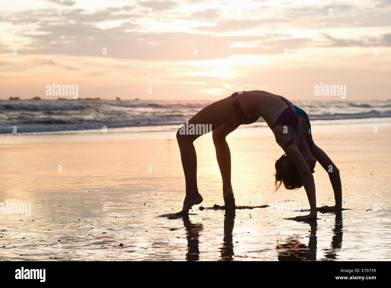 Mid adult woman bending over backwards on beach at sunset, Nosara, Guanacaste, Costa Rica - Stock Image