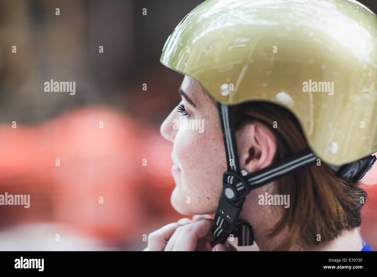 Close up of mid adult woman cyclist fastening cycle helmet - Stock Image