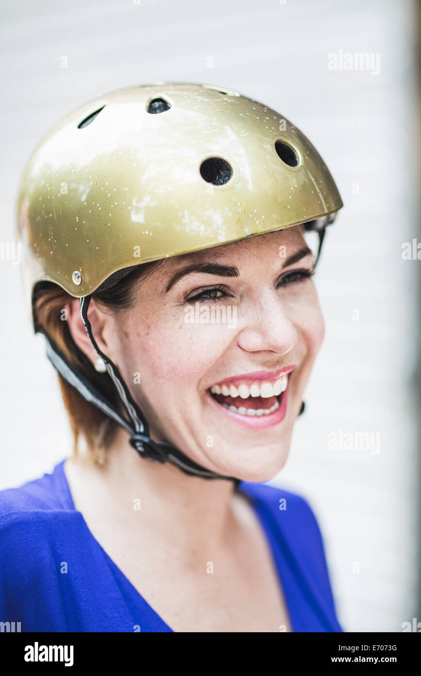 Portrait of smiling mid adult woman cyclist wearing cycle helmet - Stock Image