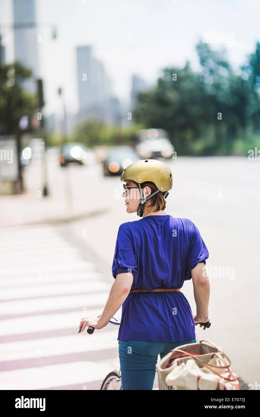 Mid adult woman cyclist waiting at pedestrian crossing, New York City, USA - Stock Image
