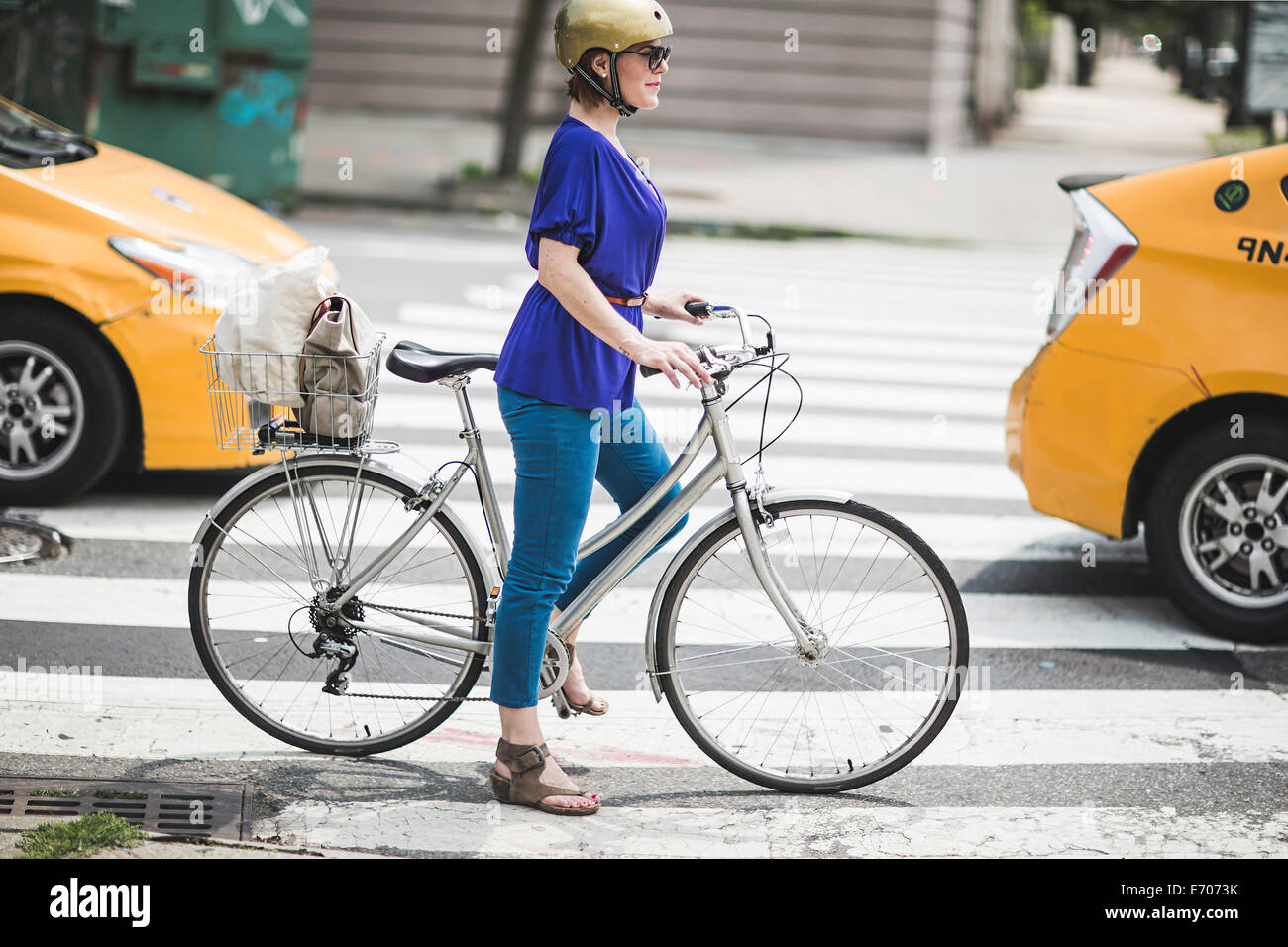 Mid adult woman cyclist waiting on pedestrian crossing, New York City, USA - Stock Image