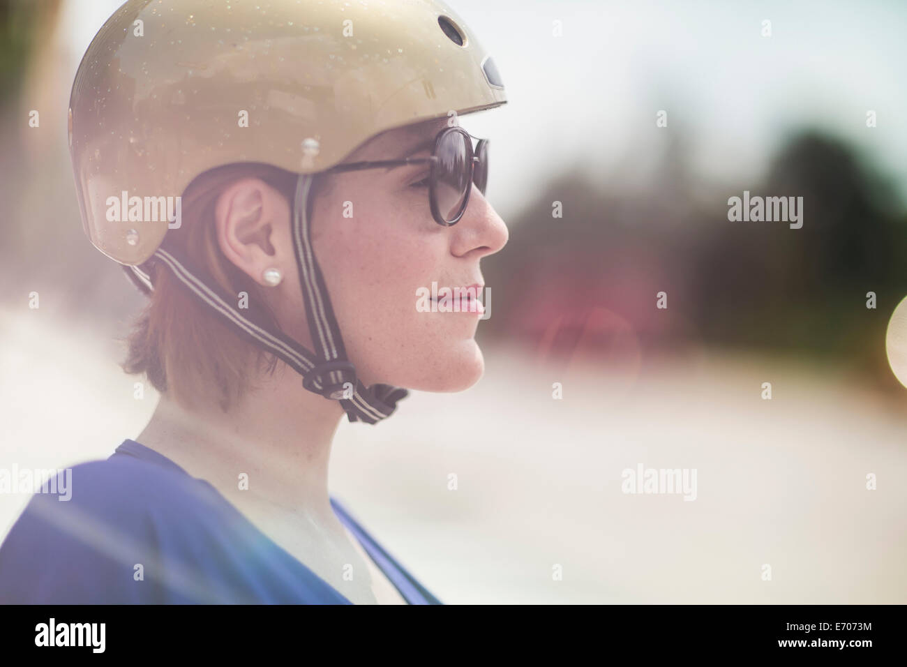 Close up of mid adult woman cyclist wearing cycle helmet and sunglasses - Stock Image