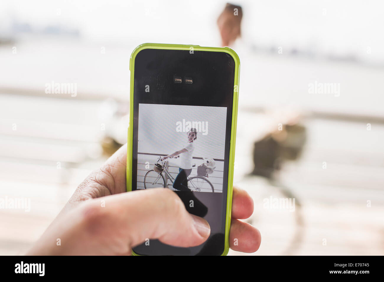 Male hand photographing girlfriend and bicycle with smartphone at riverside, New York City, USA - Stock Image