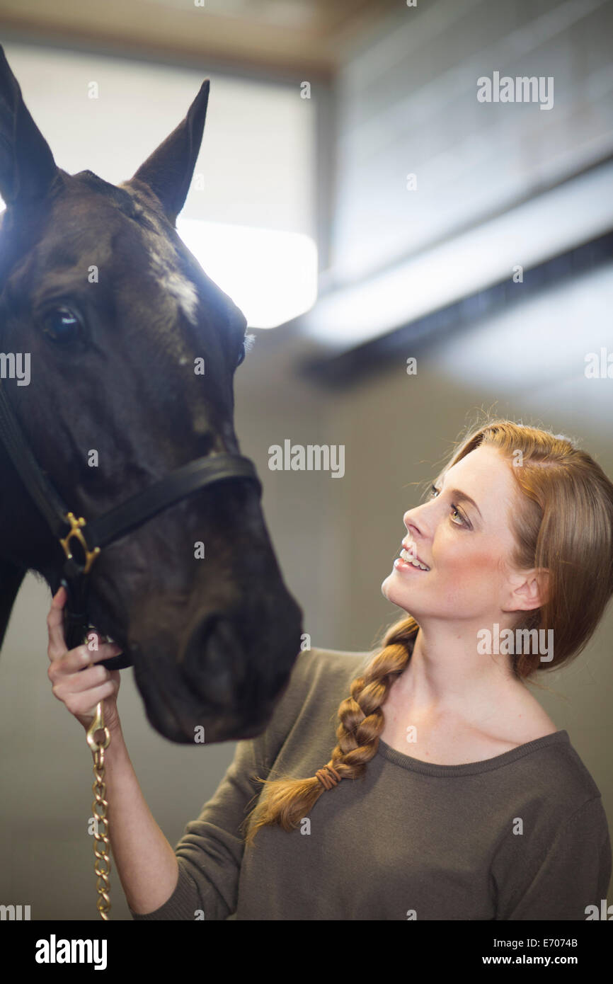 Portrait of female stablehand with horse in stables - Stock Image