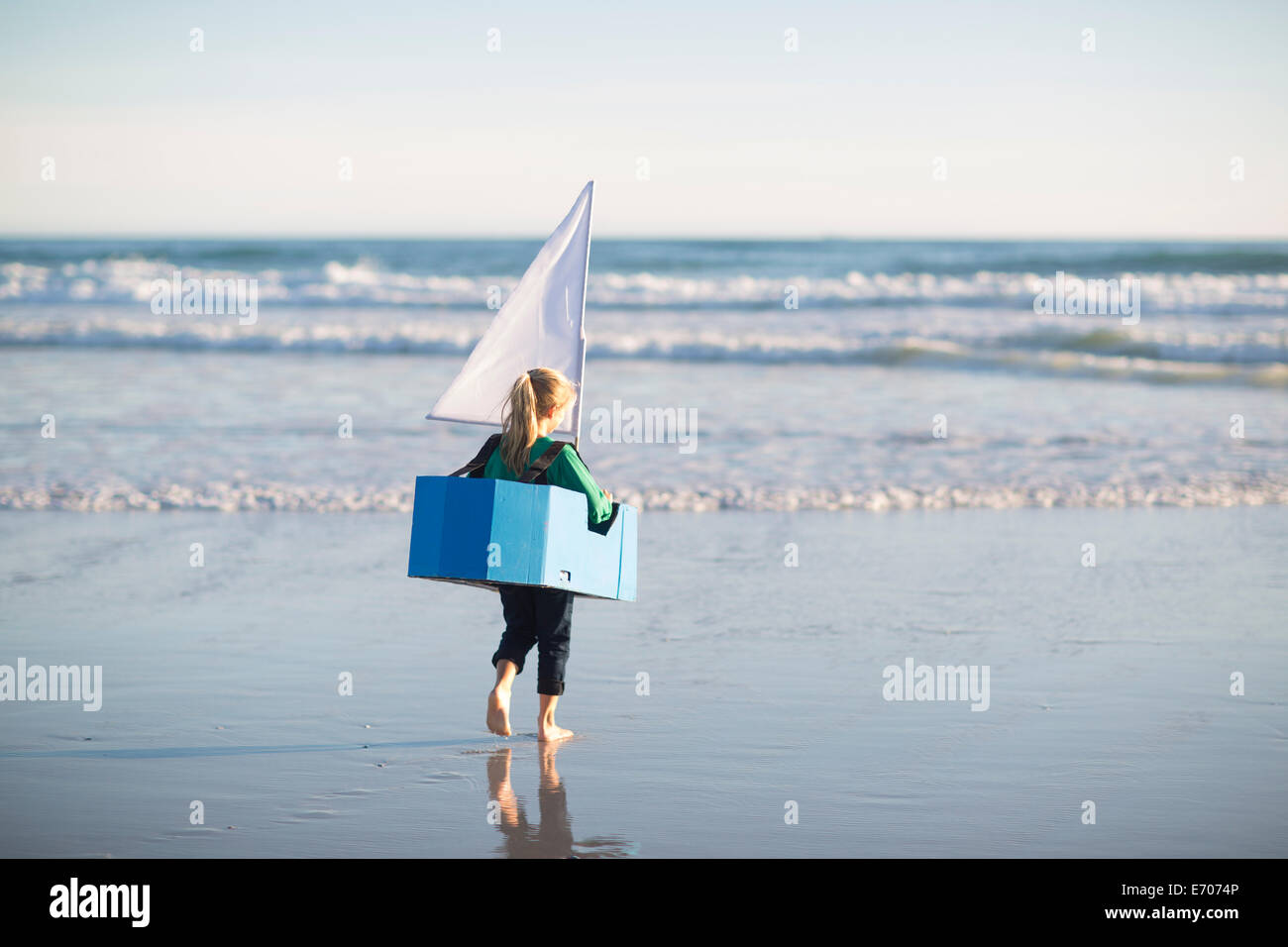 Girl running with toy boat into sea Stock Photo