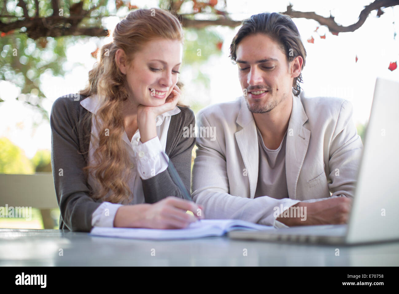 Businessman and female colleague making notes during informal meeting in garden - Stock Image
