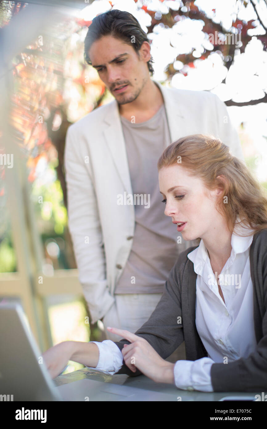 Businessman and female colleague looking at laptop during informal meeting in garden - Stock Image