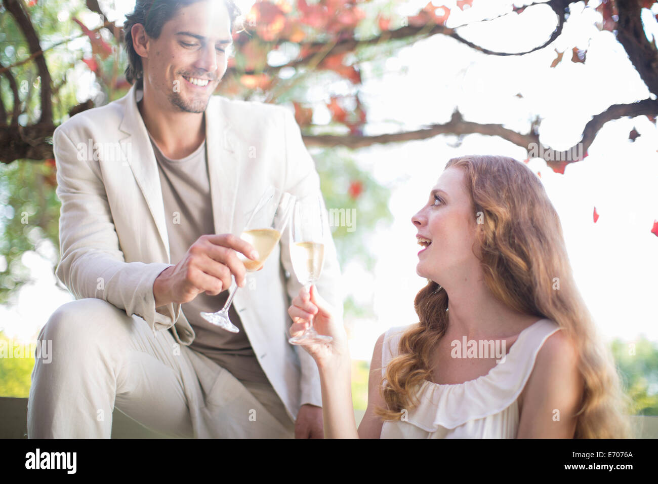 Couple toasting each other with champagne in garden restaurant - Stock Image