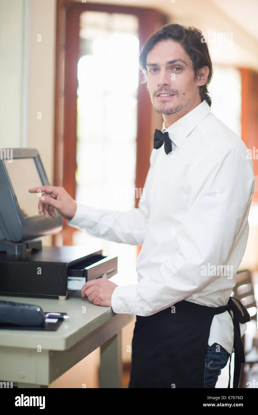 Portrait of waiter using touch screen on cash register in restaurant - Stock Image