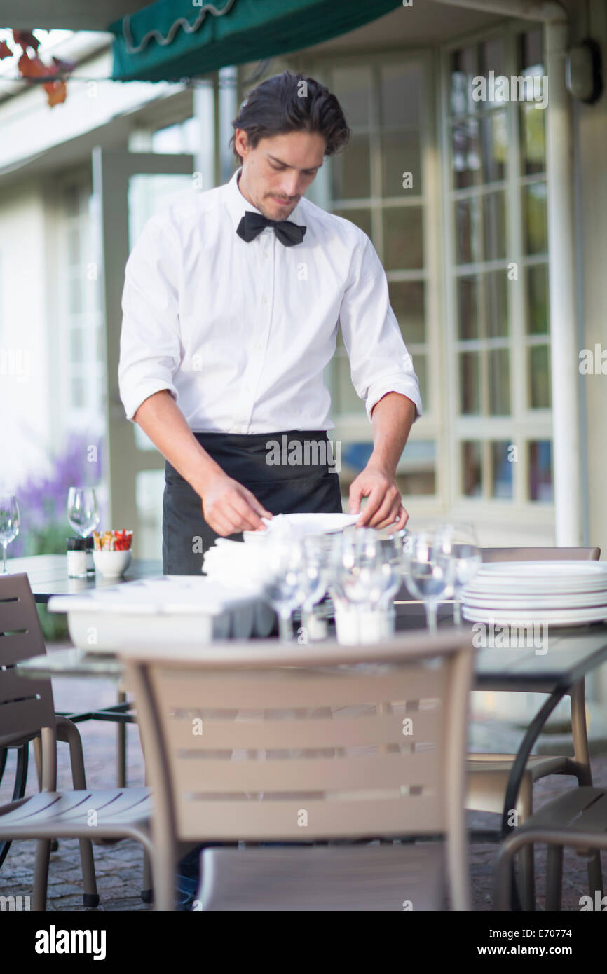 Waiter folding napkins in patio restaurant - Stock Image