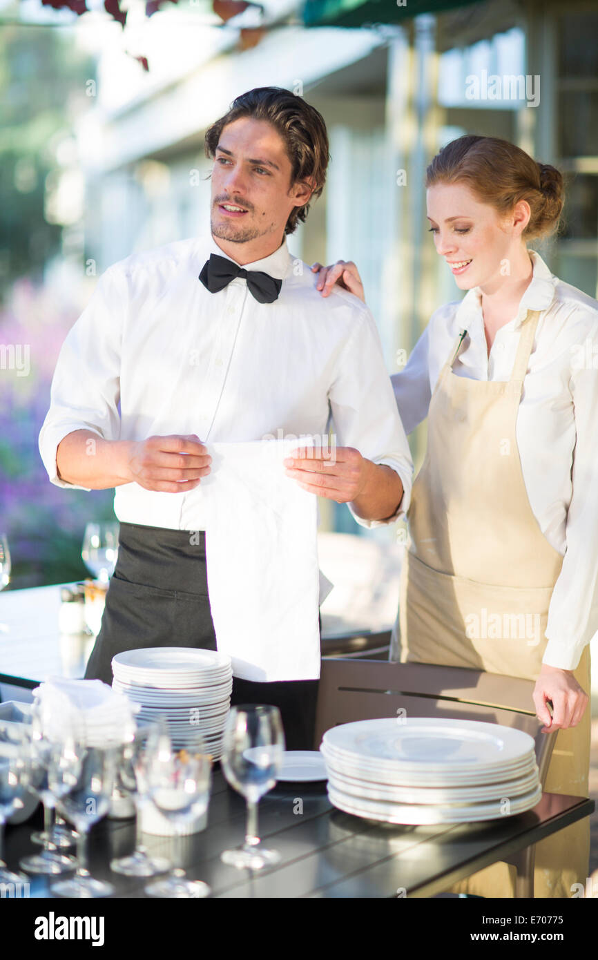 Waiter and waitress setting up tables in patio restaurant - Stock Image