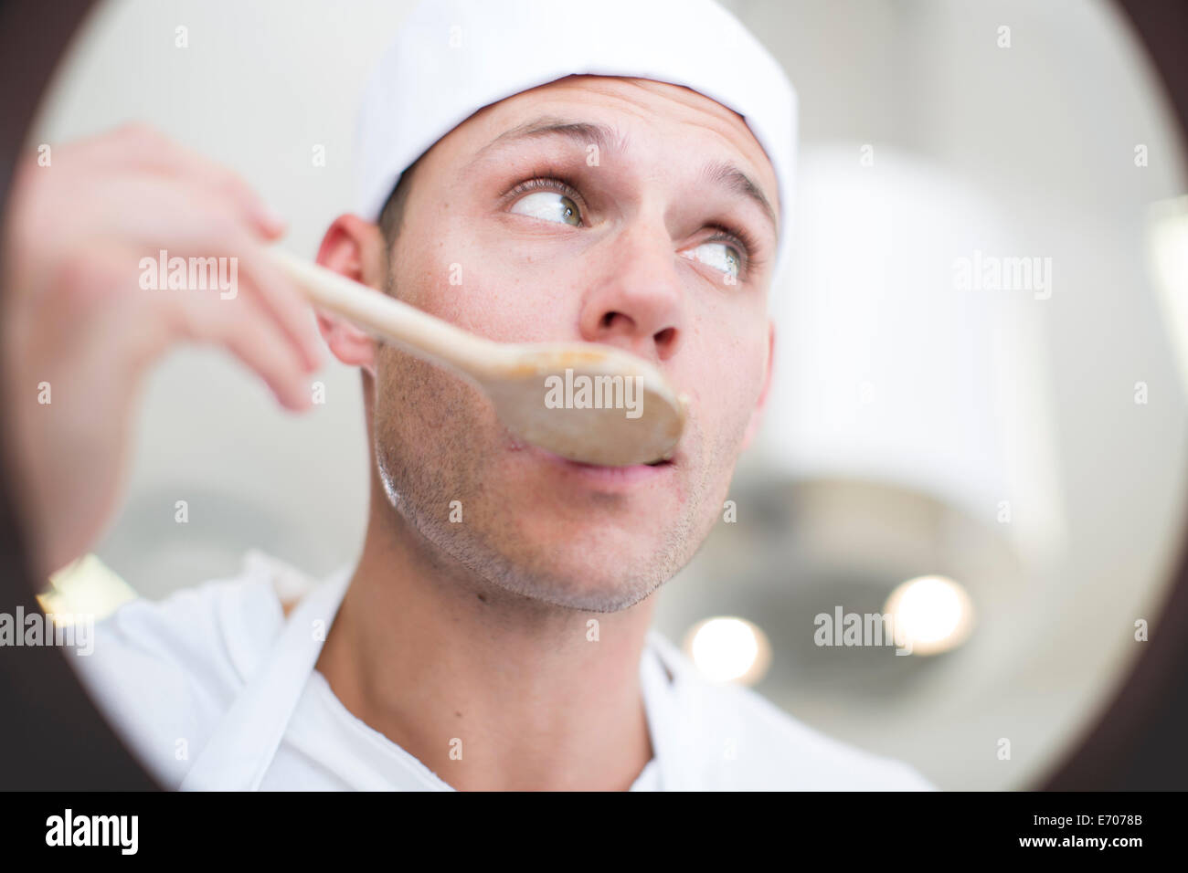Male chef tasting food from saucepan in commercial kitchen Stock Photo