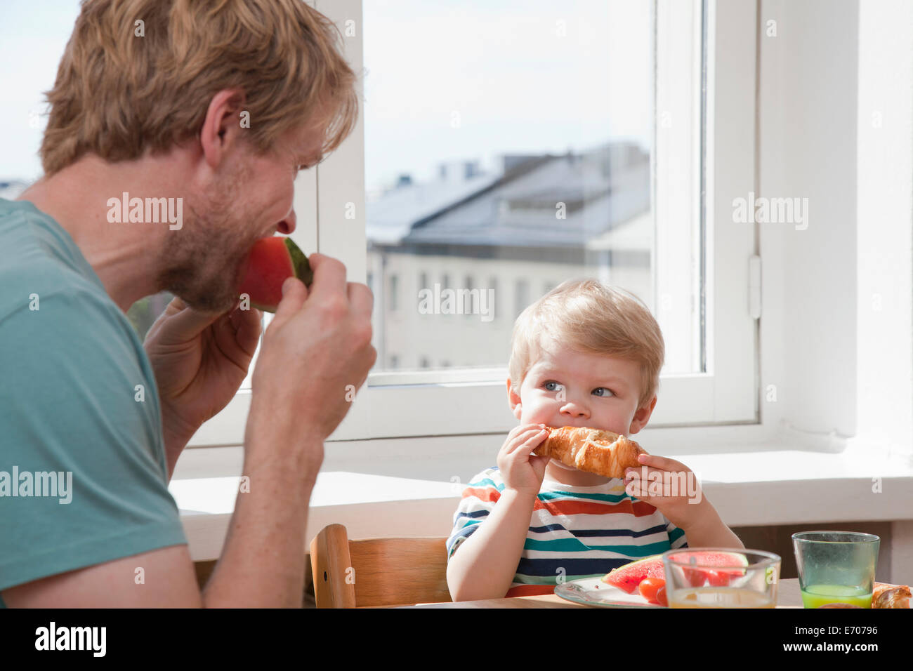 Father and toddler son eating breakfast at kitchen table Stock Photo