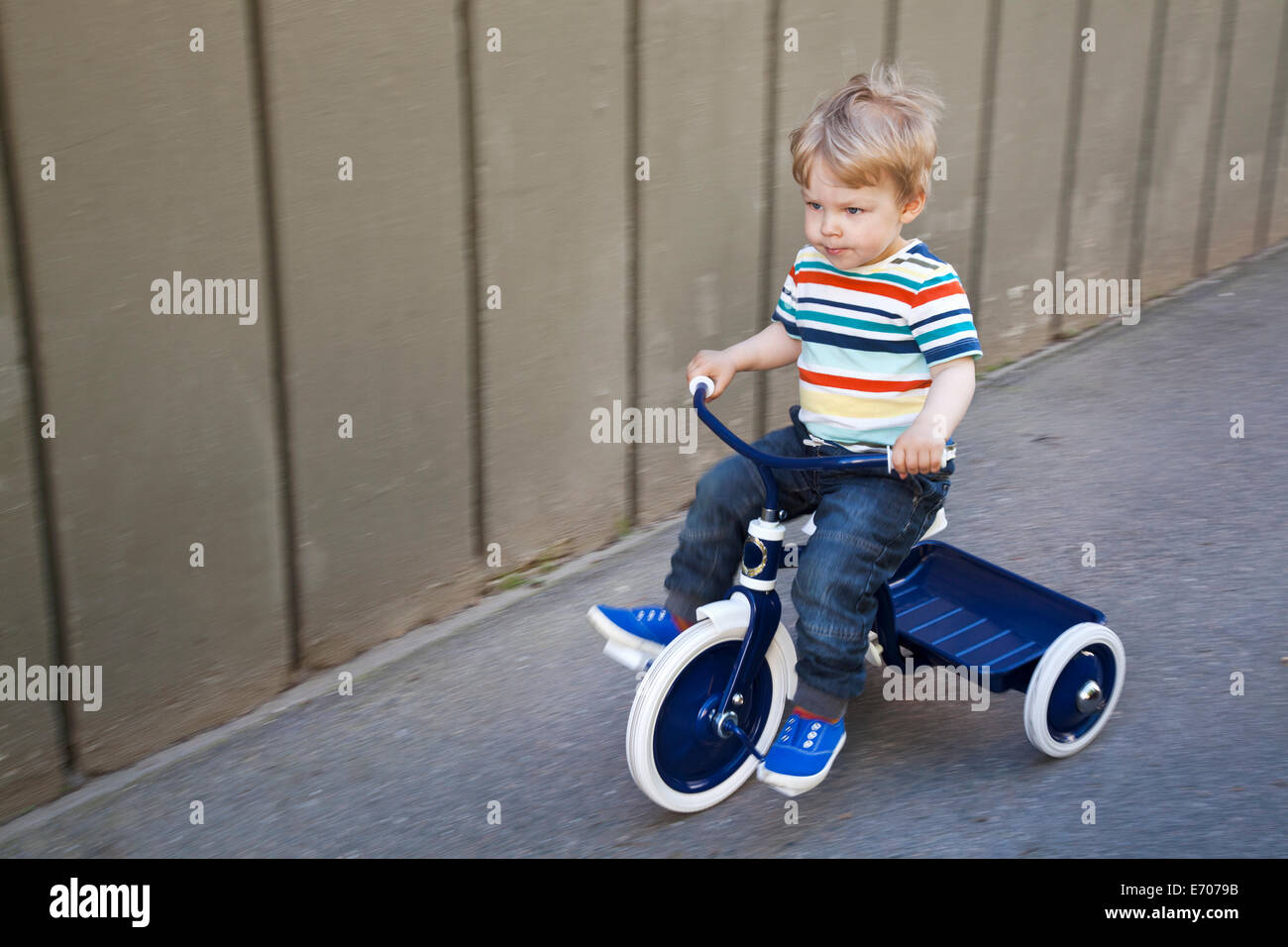 Male toddler playing on tricycle in garden - Stock Image