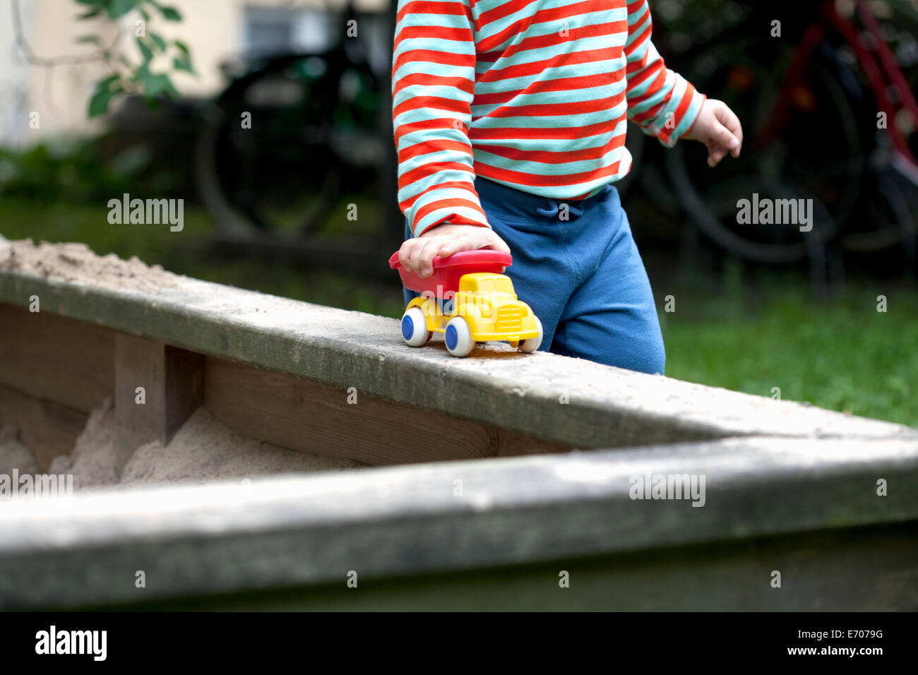 Cropped shot of male toddler pushing toy car around sand pit in garden - Stock Image