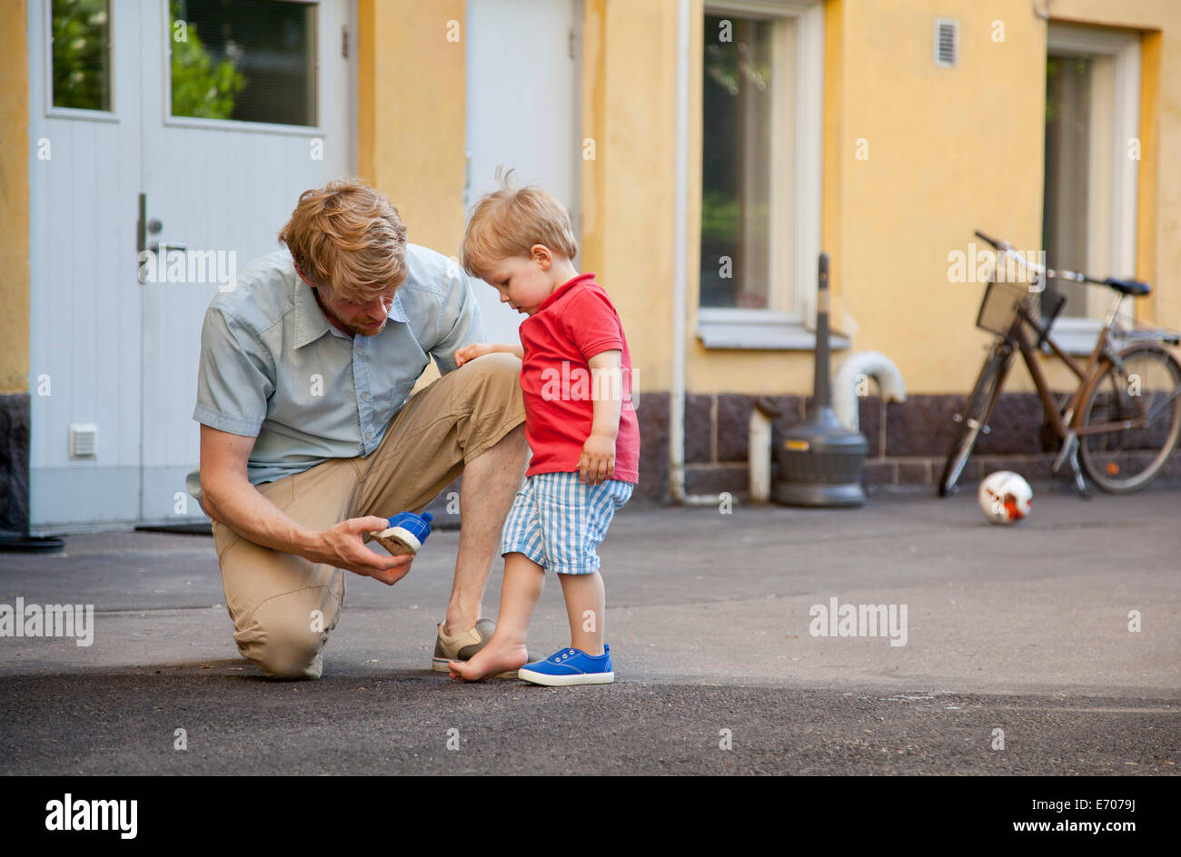 Father giving toddler son a hand to put on trainer in garden - Stock Image