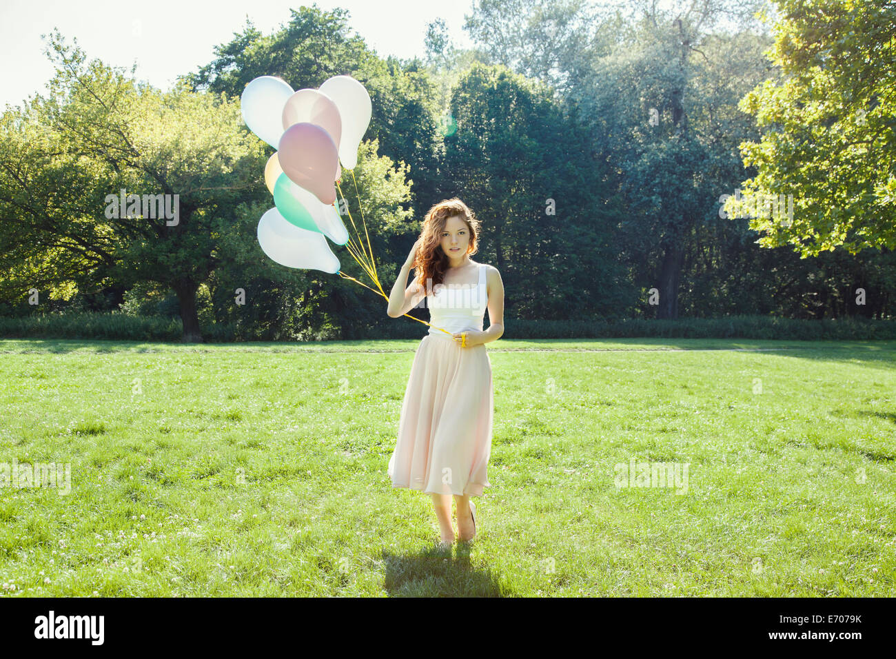 Portrait of shy young woman in park holding a bunch of balloons - Stock Image