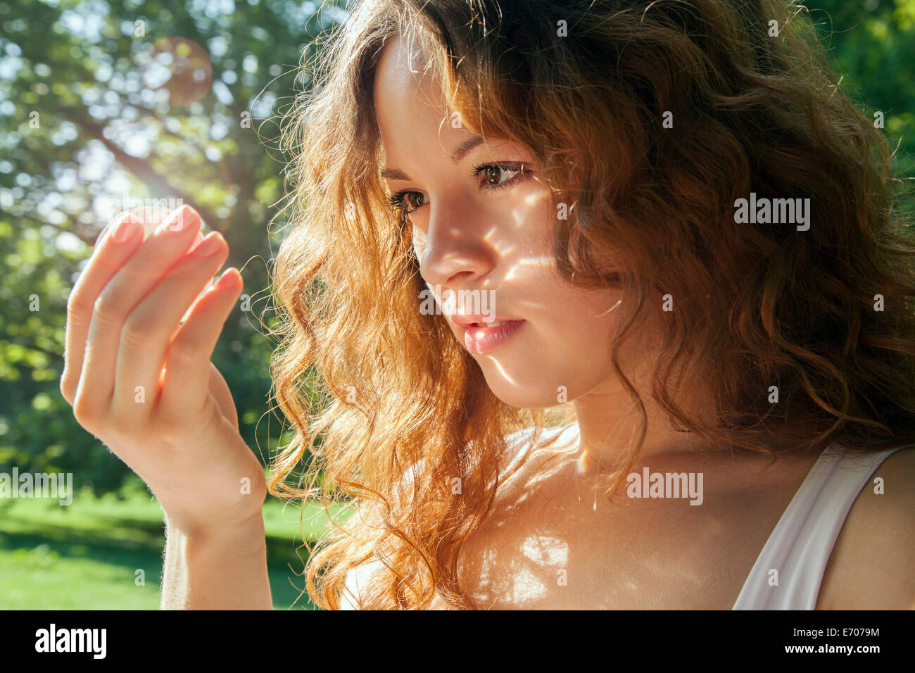 Portrait of young woman gazing at something glowing in hand - Stock Image