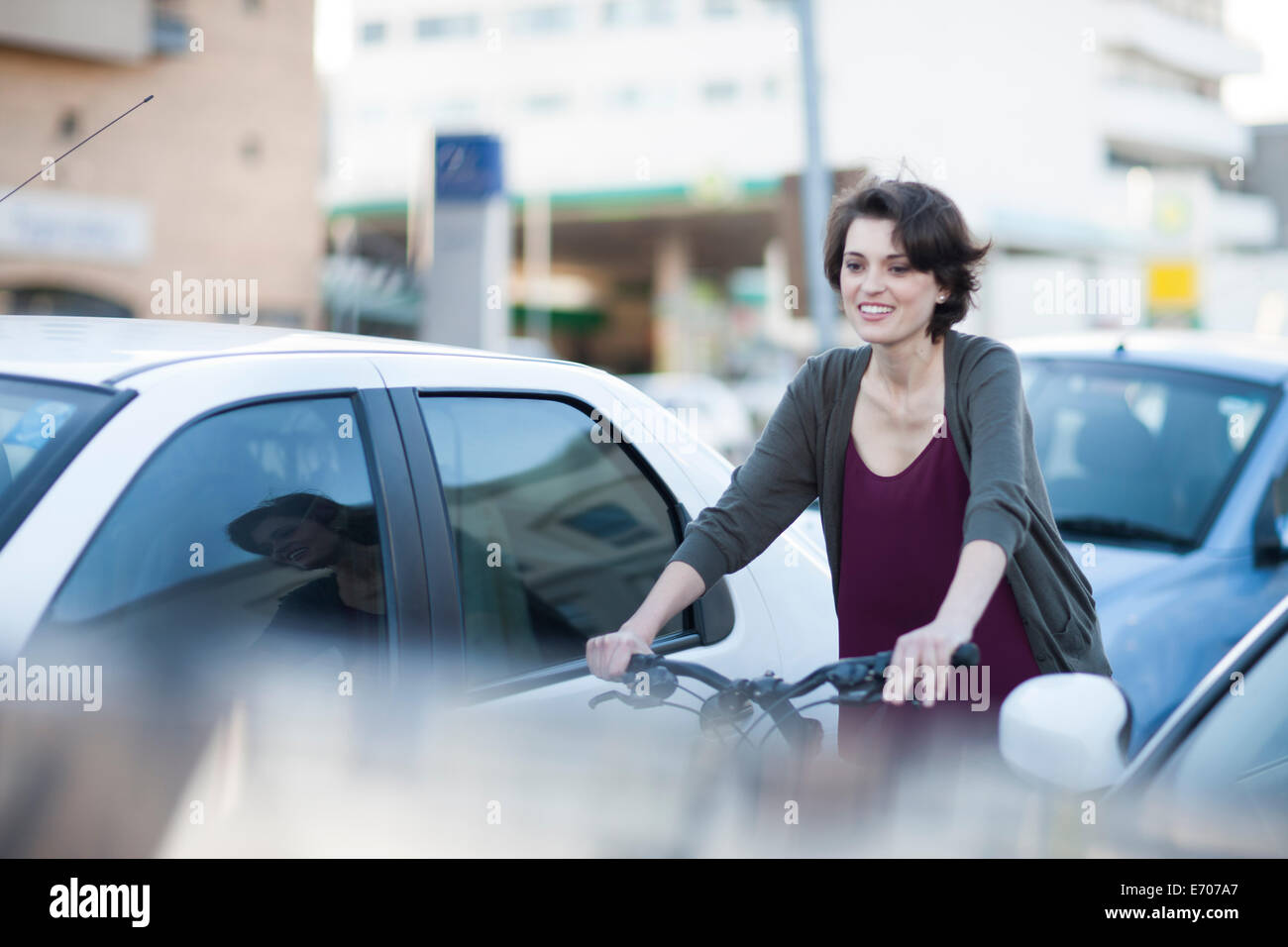 Young female cyclist commuting through city traffic jam - Stock Image