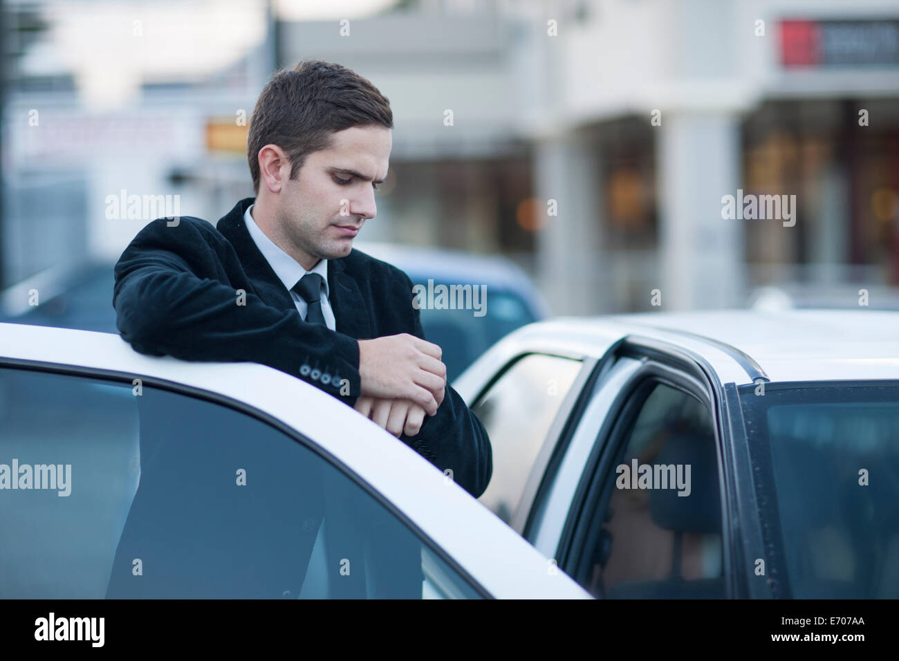 Mid adult businessman looking at watch in city traffic jam - Stock Image