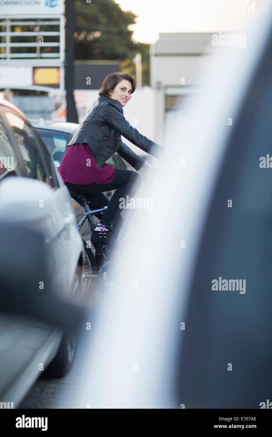 Young female cyclist commuting in city traffic jam - Stock Image