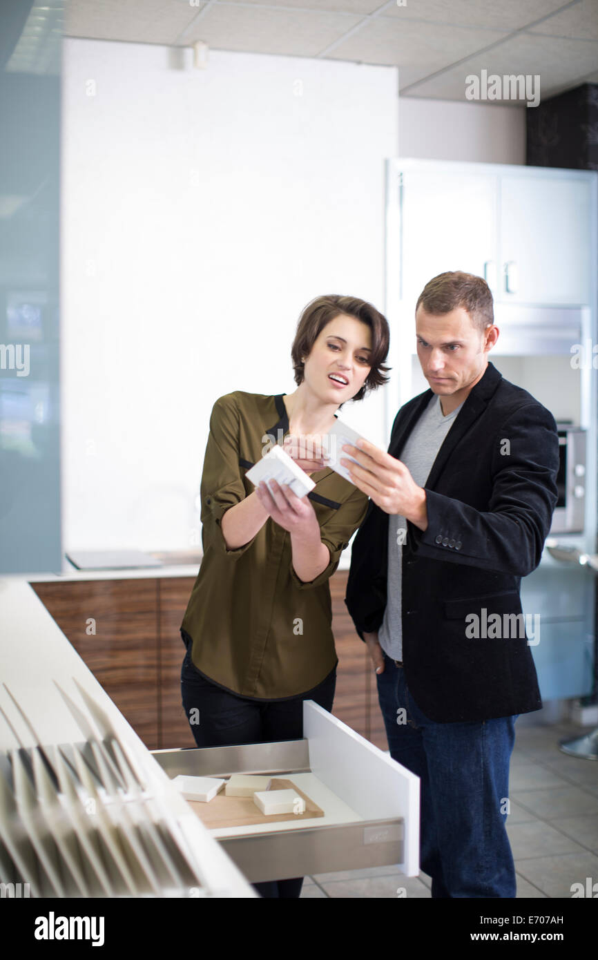 Mid adult couple comparing ceramic tiles in kitchen showroom - Stock Image