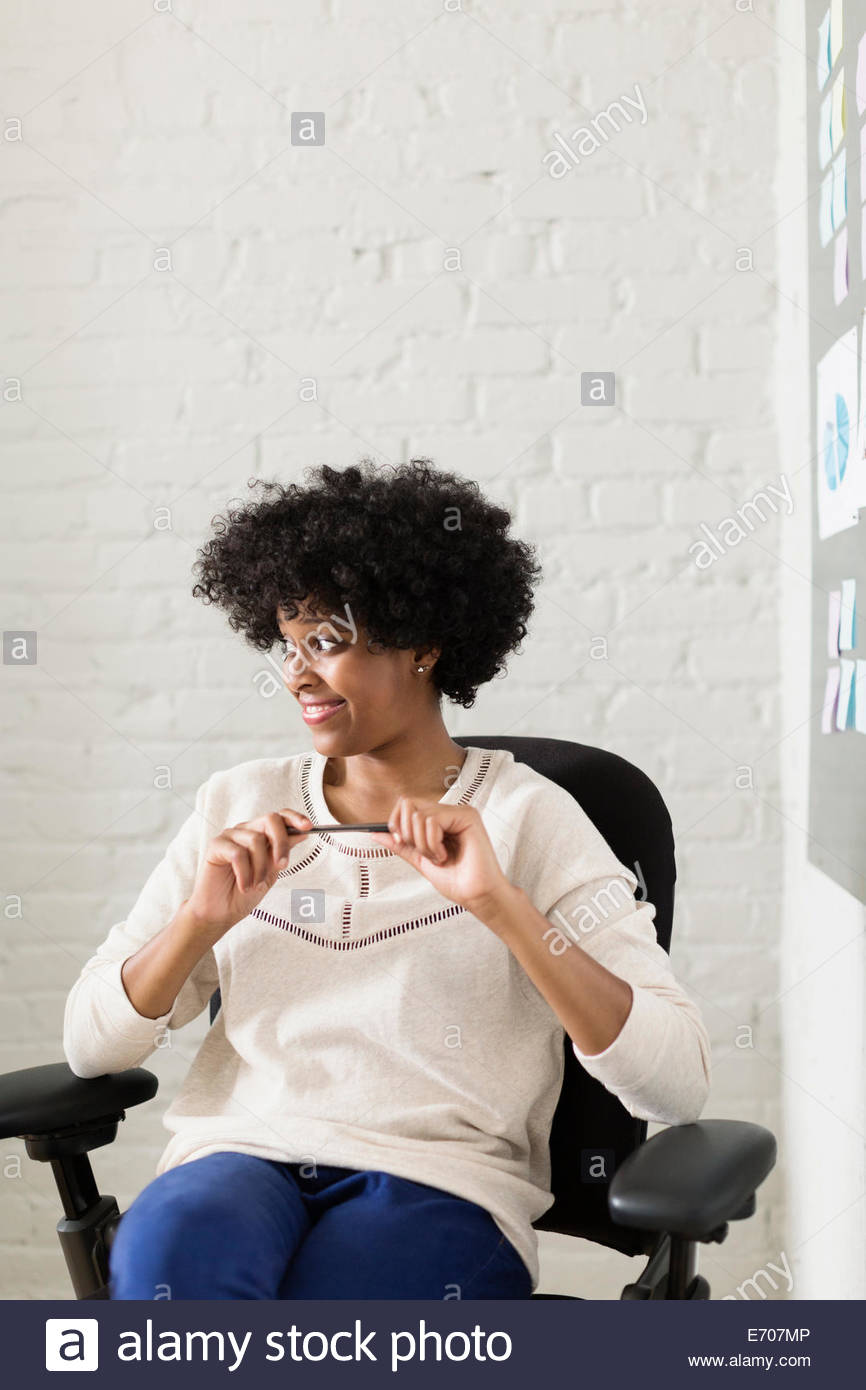 Portrait of young woman sitting in office chair looking away - Stock Image