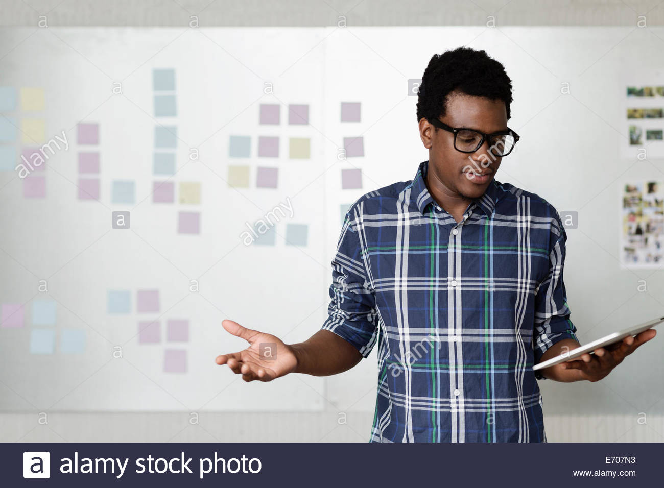 Young man holding digital tablet with arms out - Stock Image