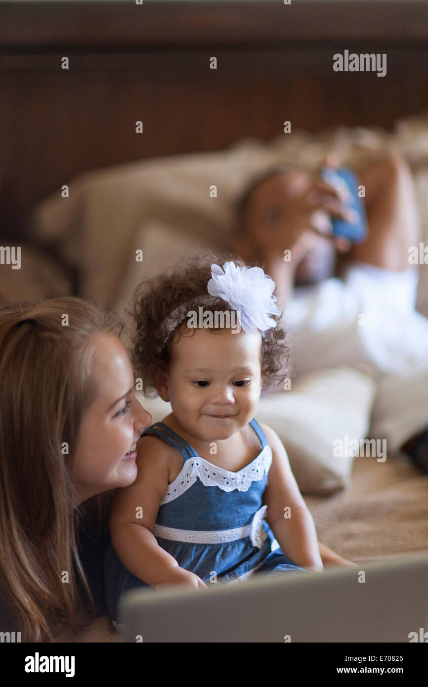 Mother showing baby daughter laptop screen Stock Photo