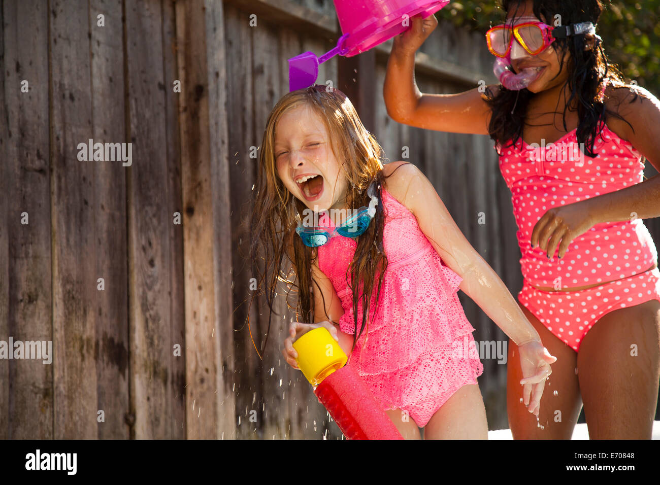 Two girls chasing each other with water in garden - Stock Image