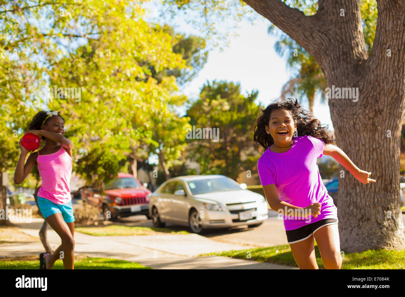 Girl chasing friend with water balloon on street - Stock Image