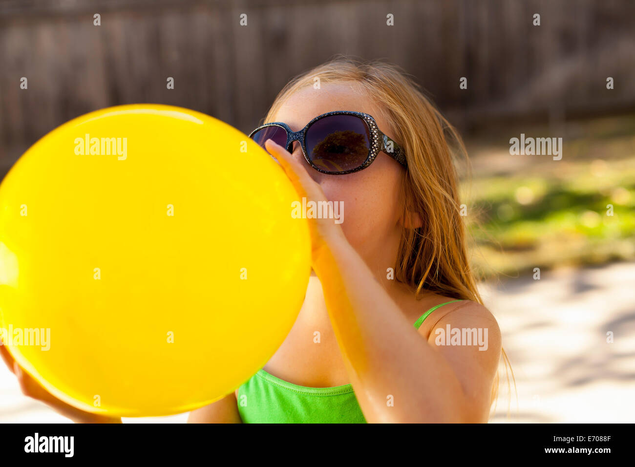 Girl inflating yellow balloon in garden - Stock Image