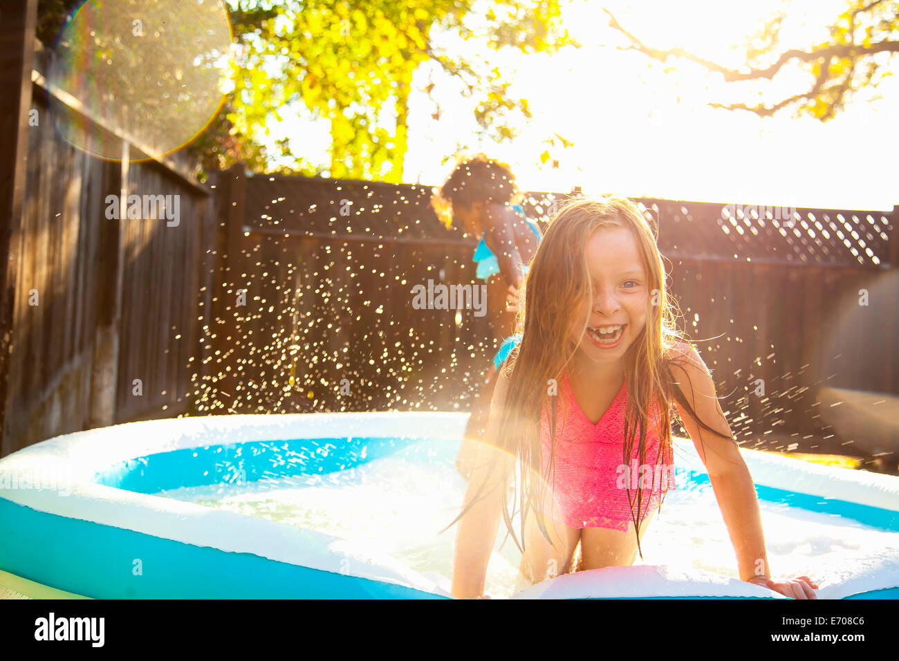 Two girls playing in garden paddling pool - Stock Image