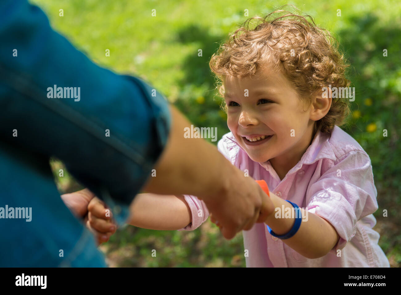 Young mother holding son's hands in park - Stock Image