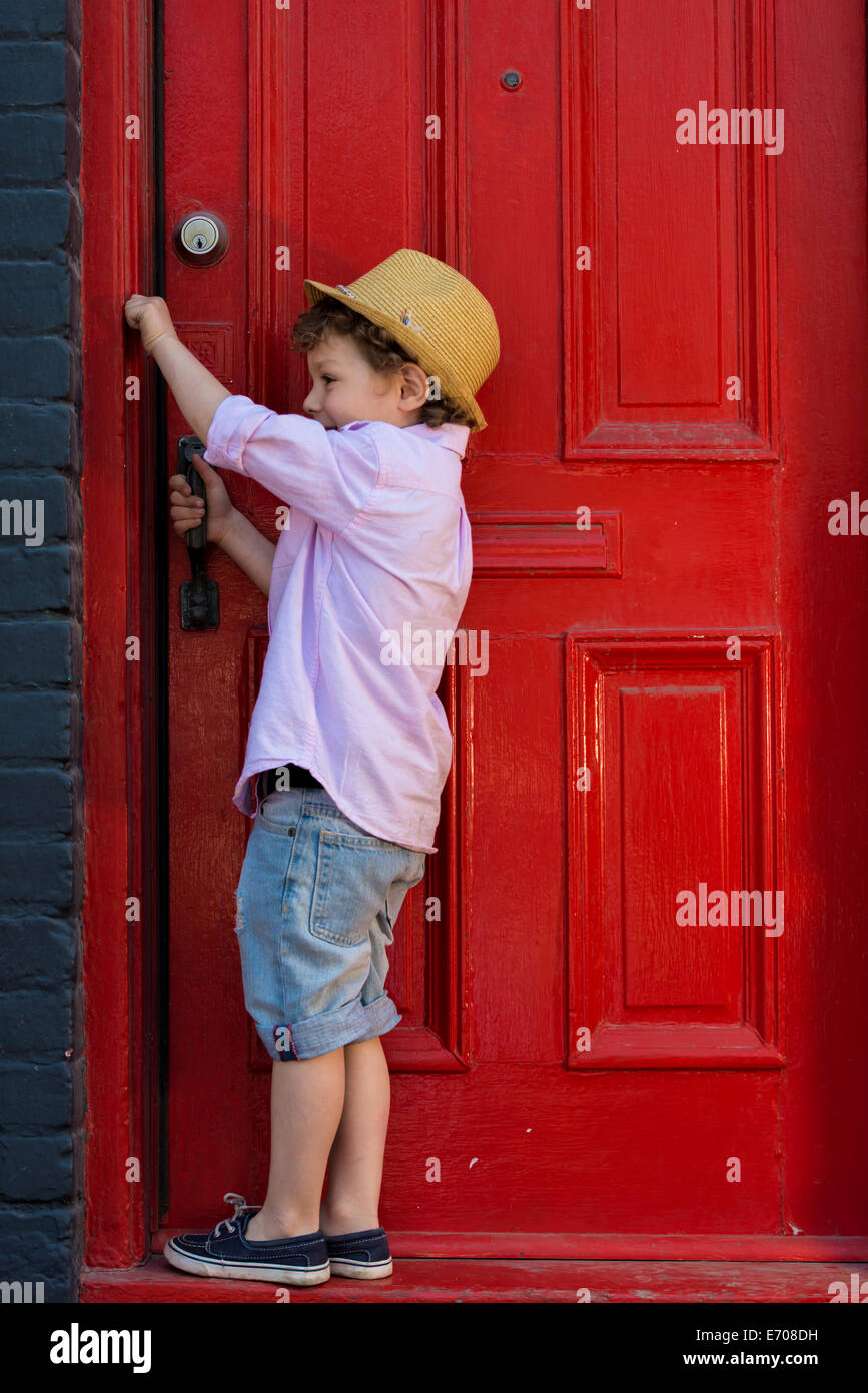 Boy opening red front door - Stock Image