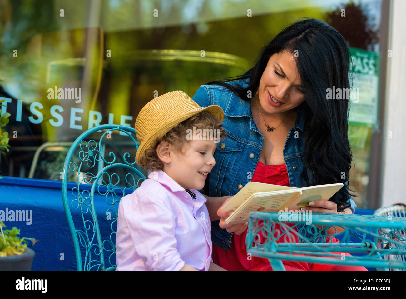 Young mother reading story book with son at sidewalk cafe - Stock Image