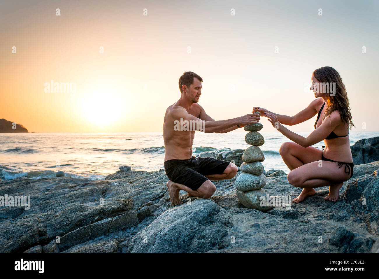 Couple on beach building tower from rocks - Stock Image