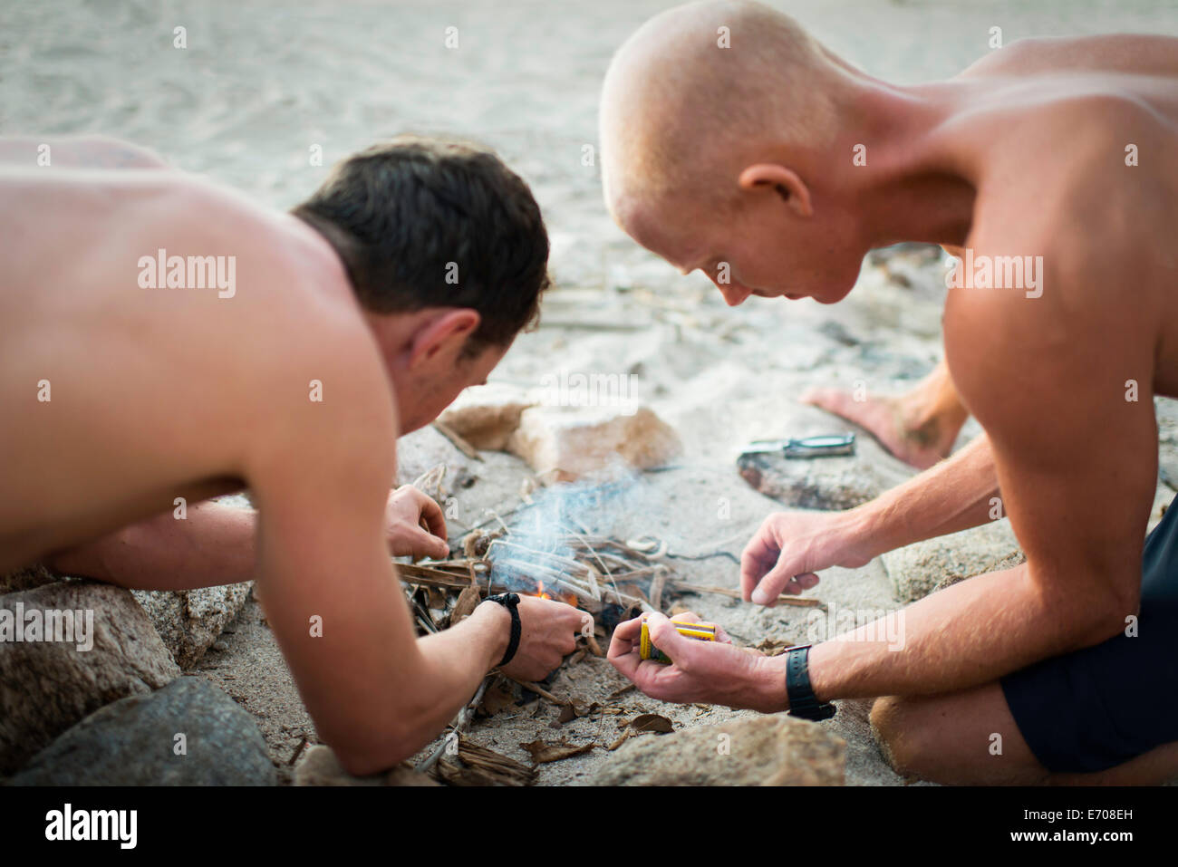 Two mid adult men lighting bonfire on beach - Stock Image