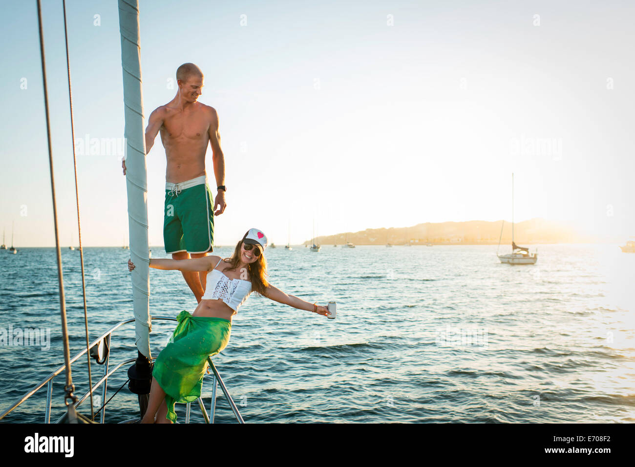 Playful mid adult couple on boat in ocean - Stock Image