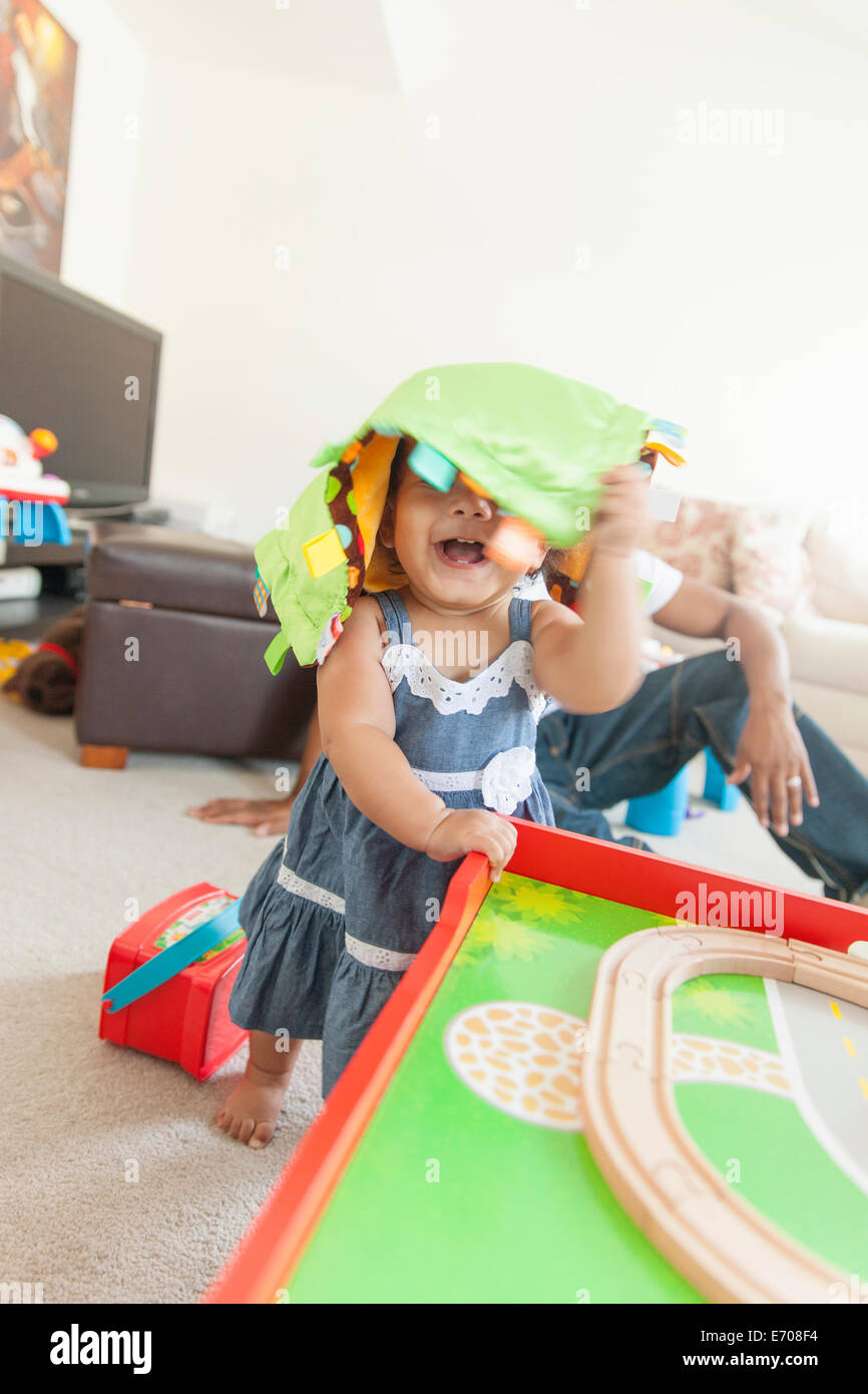 Baby girl playing, father in background - Stock Image
