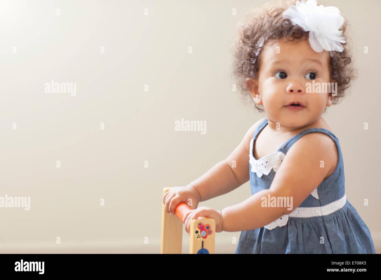 Portrait of baby girl, pushing baby walker - Stock Image