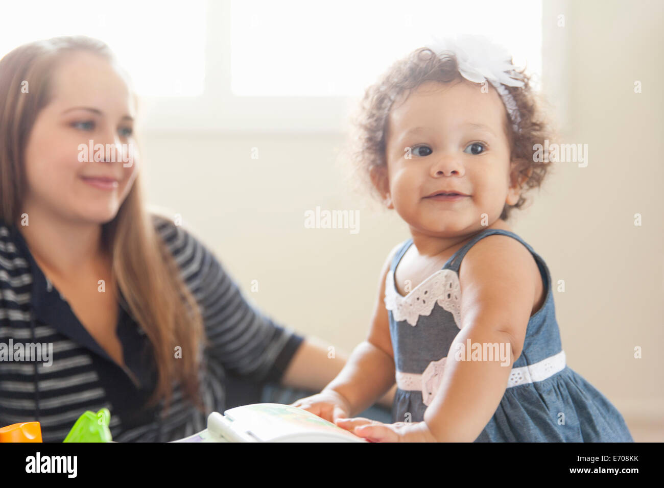 Mother watching young daughter play - Stock Image