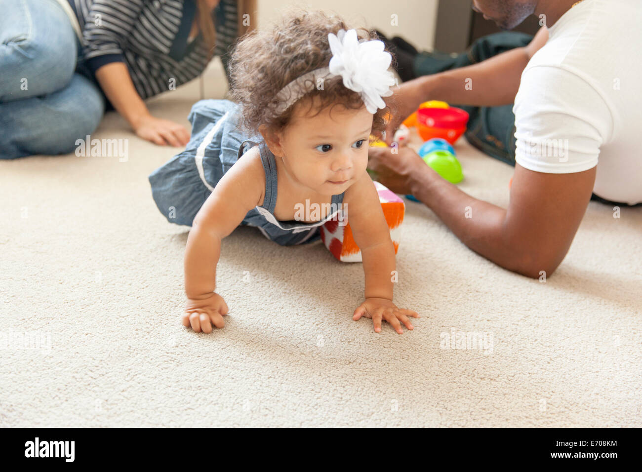 Mother and father playing with young daughter - Stock Image